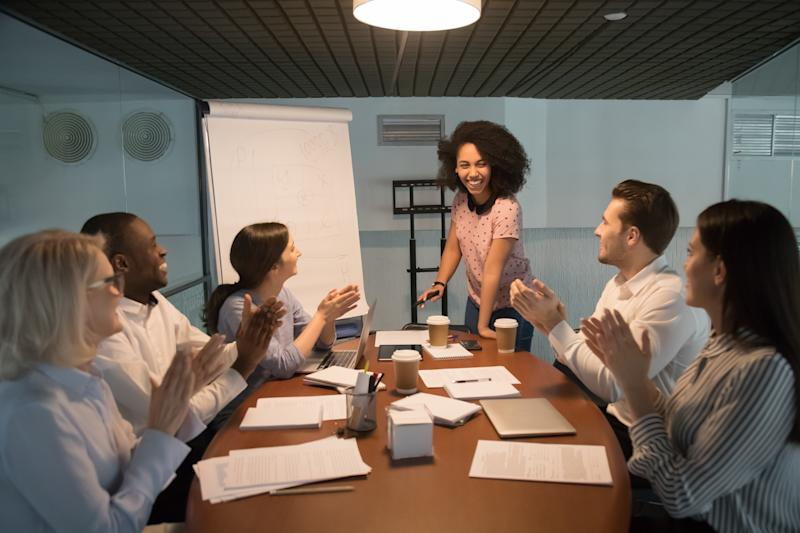 Diverse office workers gather together in modern board room sitting at desk welcoming or express gratitude biracial business coach trainer professional people starts or finish evening seminar concept