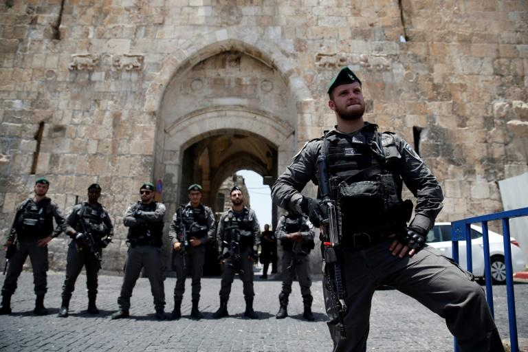 Israeli security forces stand guard as Palestinians worshippers demonstrate outside the Lions Gate, a main entrance to the Al-Aqsa mosque compound, due to new security measures by Israeli authorities, in Jerusalem's Old City on July 17, 2017
