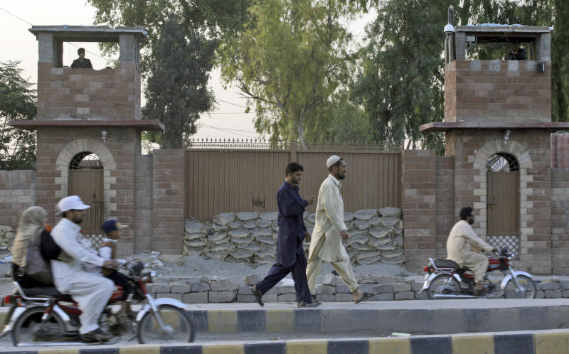 Pakistani men walk by the Central Jail in Peshawar, Pakistan, Wednesday, May 23, 2012. A Pakistani doctor who helped the U.S. track down Osama bin Laden was sentenced to 33 years in prison on Wednesday for conspiring against the state, officials said, a verdict that is likely to further strain the country's relationship with Washington. (AP Photo/Mohammad Sajjad)