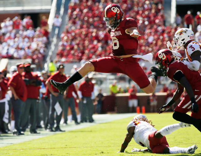 FILE - In this Oct. 7, 2017, file photo, Oklahoma quarterback Baker Mayfield (6) leaps over Iowa State defensive back De'Monte Ruth, bottom, in the second quarter of an NCAA college football game in Norman, Okla. Mayfield is expected to be a first round pick in the NFL Draft. (AP Photo/Sue Ogrocki, File)
