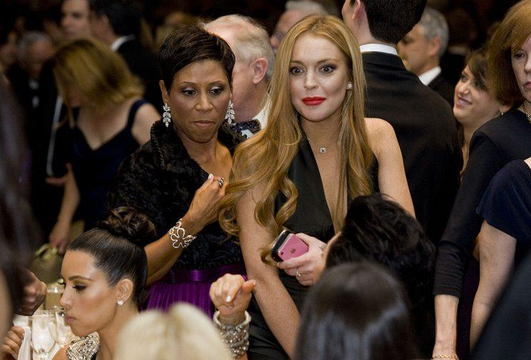 Lindsay Lohan, with her attorney Shawn Chapman Holley, arriving at her table, where Kim Kardashian was parked, in 2012. (Photo: Kristoffer Tripplaar-Pool/Getty Images)