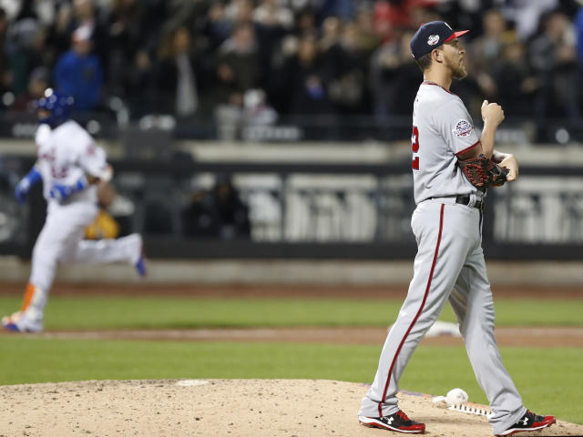 Washington Nationals starting pitcher A.J. Cole, right, looks to the outfield as New York Mets' Yoenis Cespedes, left, runs the bases after hitting a grand slam in the eighth inning of a baseball game, Wednesday, April 18, 2018, in New York. (AP Photo/Kathy Willens)