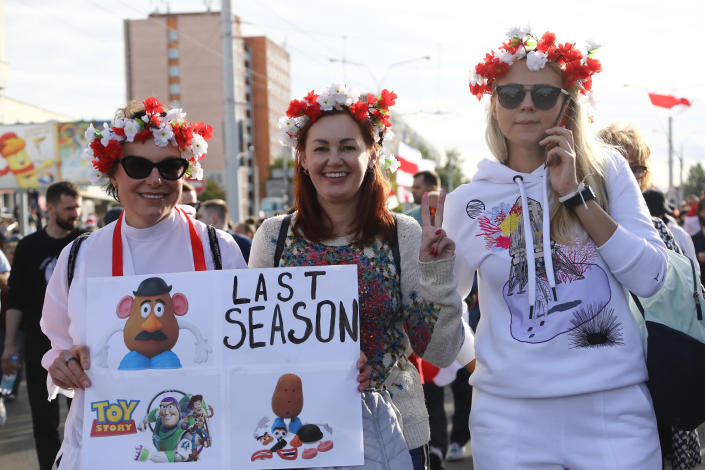 Women with a wreath on their heads pose for a photo during a Belarusian opposition supporters' rally protesting the official presidential election results in Minsk, Belarus, Sunday, Sept. 13, 2020. Protests calling for the Belarusian president's resignation have broken out daily since the Aug. 9 presidential election that officials say handed him a sixth term in office. (TUT.by via AP)