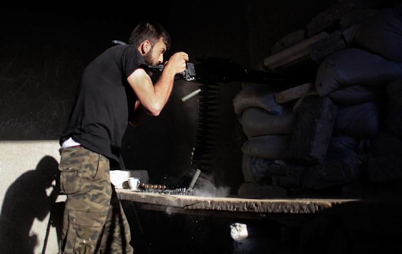 A rebel fighter fires a heavy machine gun during fighting with Syrian pro-government forces on a front line in the northern city of Aleppo, on July 8, 2014 (AFP Photo/Ahmed Deeb)