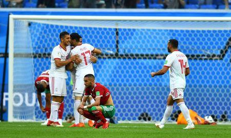 Soccer Football - World Cup - Group B - Morocco vs Iran - Saint Petersburg Stadium, Saint Petersburg, Russia - June 15, 2018 Morocco's Hakim Ziyech looks dejected as Iran's Mehdi Taremi and team mates celebrate at the end of the match REUTERS/Dylan Martinez
