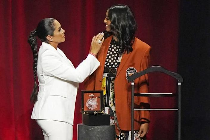 Vanessa Bryant, left, widow of Kobe Bryant presents their daughter Natalia with Bryant's Hall of Fame jacket at the 2020 Basketball Hall of Fame awards tip-off celebration and awards gala, Friday, May 14, 2021, in Uncasville, Conn. (AP Photo/Kathy Willens)