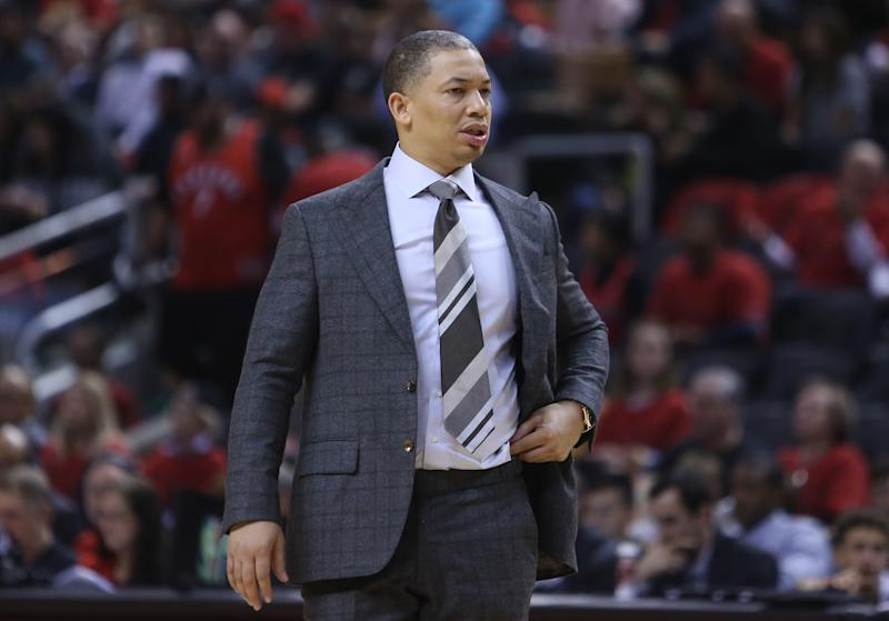 Tyronn Lue coaches from the sideline of a game.