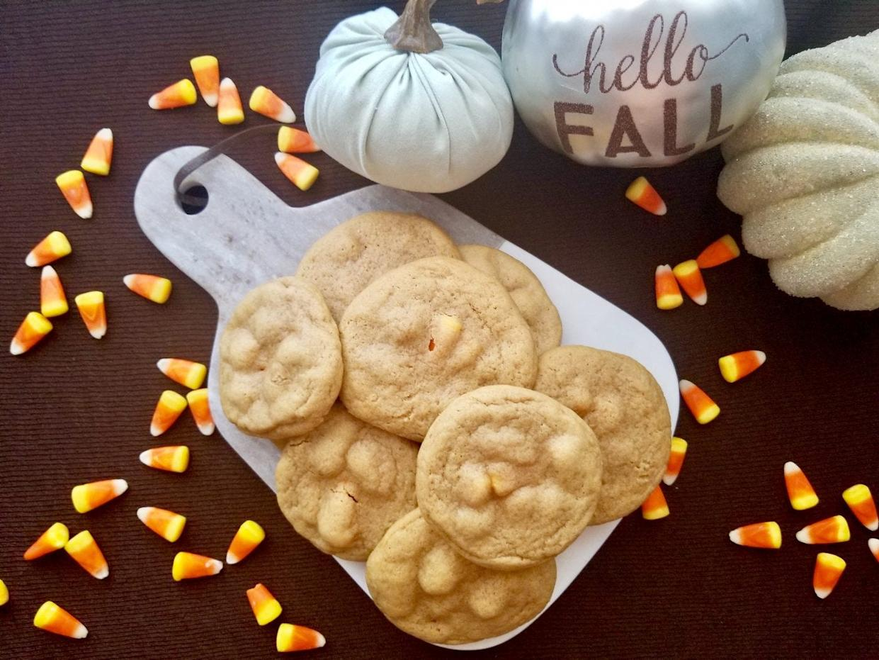 Candy corn-stuffed cookies flat lay with fall decor.