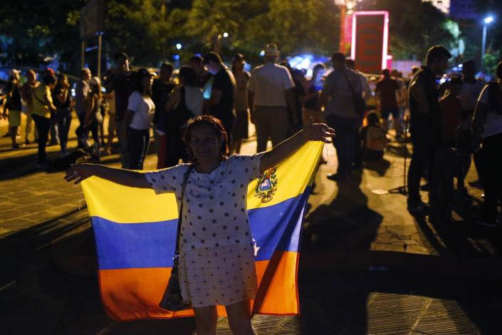 A woman holds up a Venezuelan flag as she gathers with other anti-government Venezuelan protesters at Democracy Square in Asuncion, Paraguay, Wednesday, Jan. 23, 2019. Venezuelan migrants held a rally against Venezuelan President Nicolas Maduro and in favor of Juan Guaido, head of Venezuela's opposition-run congress who today declared himself interim president of the South American nation. (AP Photo/Jorge Saenz)