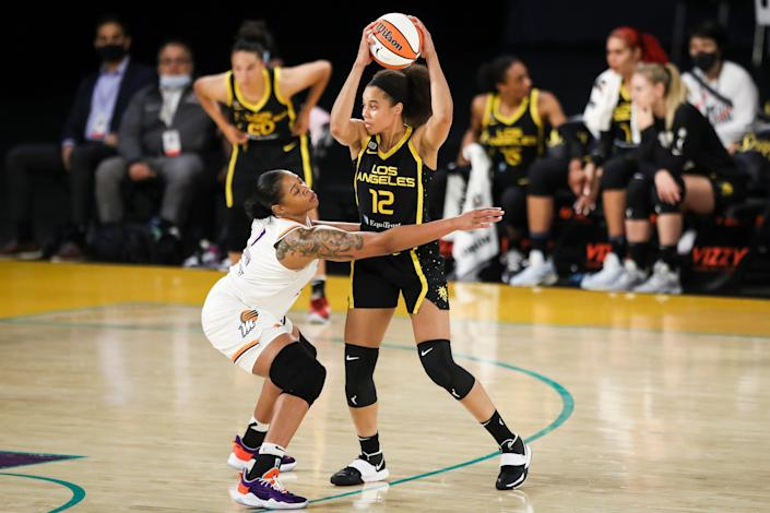 A basketball player hold the ball over her head as another player reaches out her arm to block her.