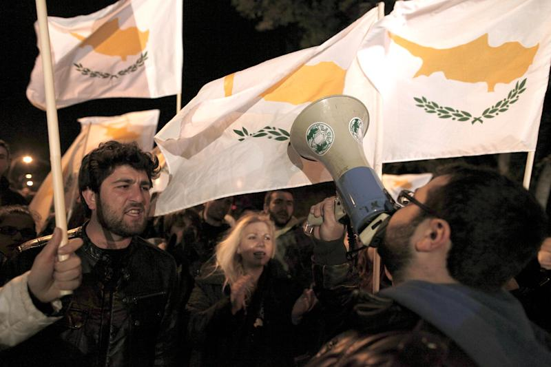 "Protesters chant slogans and wave Cypriot flags outside the Cypriot parliament, Friday, March 22, 2013. Cypriot authorities were putting the final touches Friday to a plan they hope will convince international lenders to provide the money the country urgently needed to avoid bankruptcy within days. ""The next few hours will determine the future of this country,"" said government spokesman Christos Stylianides.(AP Photo/Petros Giannakouris)"