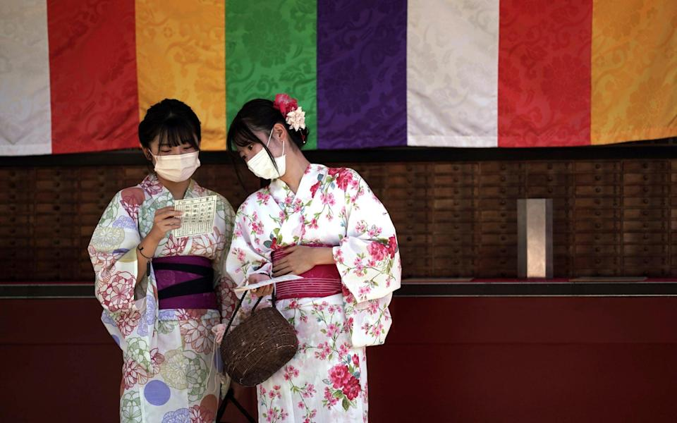 Visitors in yukatas or Japanese traditional summer kimonos wear face masks as they draw a fortune-telling paper strip at the Sensoji Temple in the Asakusa district of Tokyo on 20 September 2021 - Eugene Hoshiko/AP