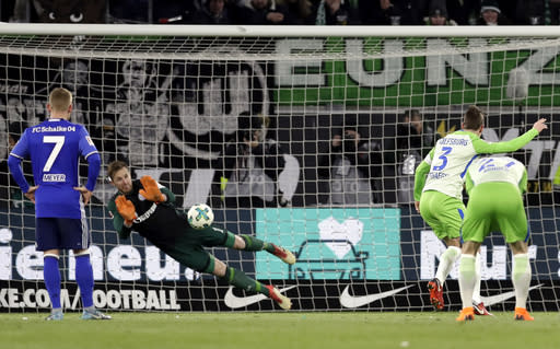 Schalke goalkeeper Ralf Faehrmann blocks a penalty shot by Wolfsburg's Paul Verhaegh, 2nd right, during the German Bundesliga soccer match between VfL Wolfsburg and FC Schalke 04 in Wolfsburg, Germany, Saturday, March 17, 2018. (AP Photo/Michael Sohn)