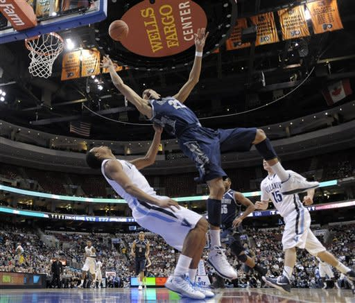 Villanova's Darrun Hilliard (4) fouls Georgetown's Otto Porter Jr. (22) as he drives to the basket in the first half of an NCAA college basketball game, Wednesday, March 6, 2013, in Philadelphia. (AP Photo/Michael Perez)