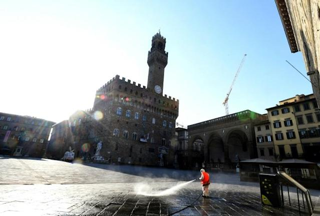 A municipal worker disinfects the Piazza della Signoria, in front of the Palazzo Vecchio, in Florence, on March, 21 2020, as part of measures taken by the Italian government to fight against the spread of the COVID-19 (novel coronavirus). (AFP Photo/Carlo BRESSAN)