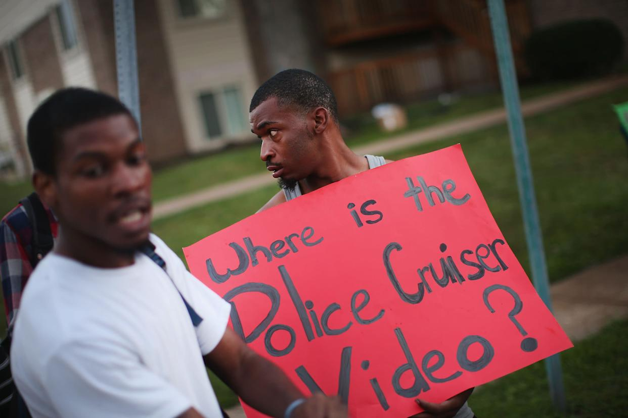 FERGUSON, MO - AUGUST 11: Demonstrators protest next to the spot where 18-year-old Michael Brown was shot by police on Saturday on August 11, 2014 in Ferguson, Missouri. Police responded with tear gas and rubber bullets as residents and their supporters protested the shooting by police of an unarmed black teenager named Michael Brown who was killed Saturday in this suburban St. Louis community. Yesterday 32 arrests were made after protests turned into rioting and looting in Ferguson. (Photo by Scott Olson/Getty Images)