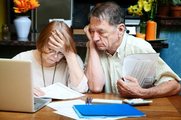 Mature couple looking worried over finances