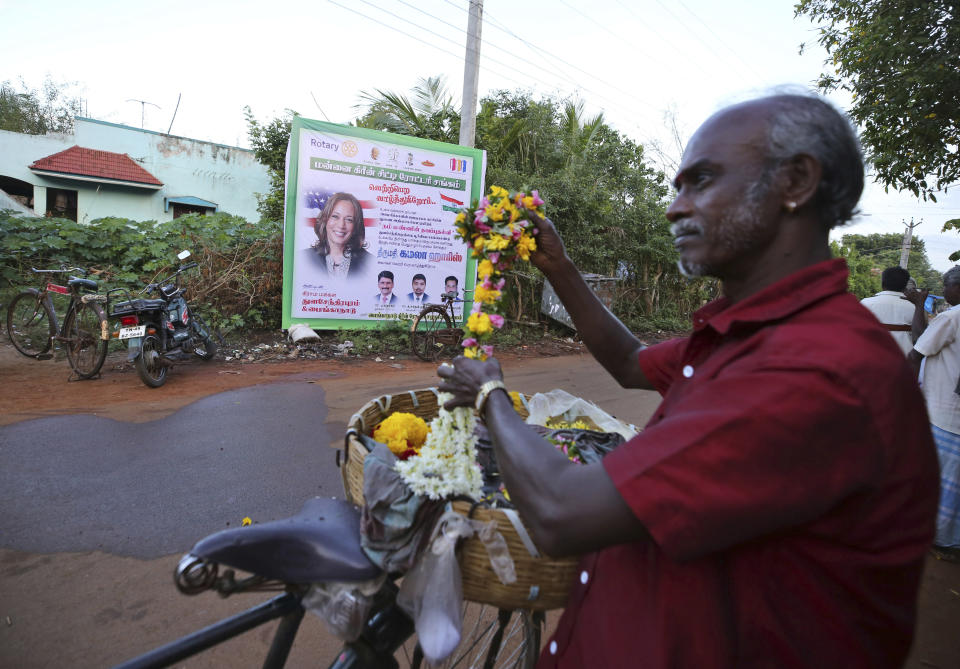 A local vendor sells flowers in front of a hoarding featuring U.S. Vice President-elect Kamala Harris in the hometown of Harris' maternal grandfather, in Thulasendrapuram, south of Chennai, Tamil Nadu state, India, Sunday, Nov. 8, 2020. After rooting for Kamala Harris as President-elect Joe Biden running mate, people in her small ancestral Indian village woke up Sunday morning to the news of her making history. (AP Photo/Aijaz Rahi)