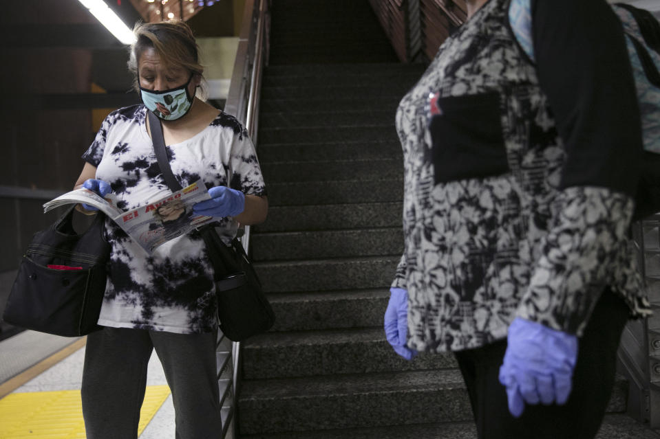 FILE - In this July 6, 2020 file photo, women with face masks and protective gloves wait for a Metro Rail train in Los Angeles during the coronavirus pandemic. To avoid any traces of the coronavirus that might be lurking on surfaces, Americans have been wiping down groceries, wearing surgical gloves in public and leaving mail packages out for an extra day or two. But experts say fear of being infected by touching something can be overblown. (AP Photo/Jae C. Hong, File)