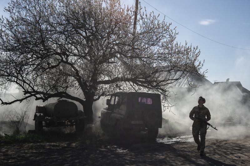 FILE - In this file photo taken on Saturday, April 20, 2019, a Ukrainian serviceman guards a position near the front line as the conflict continues, in Mariinka, Donetsk region, eastern Ukraine. Ukraine's president sits down Monday, Dec. 9, 2019 for peace talks in Paris with Russian President Vladimir Putin in their first face-to-face meeting, and the stakes could not be higher. More than five years of fighting in eastern Ukraine between government troops and Moscow-backed separatists has killed more than 14,000 people, and a cease-fire has remained elusive. (AP Photo/Evgeniy Maloletka, File)