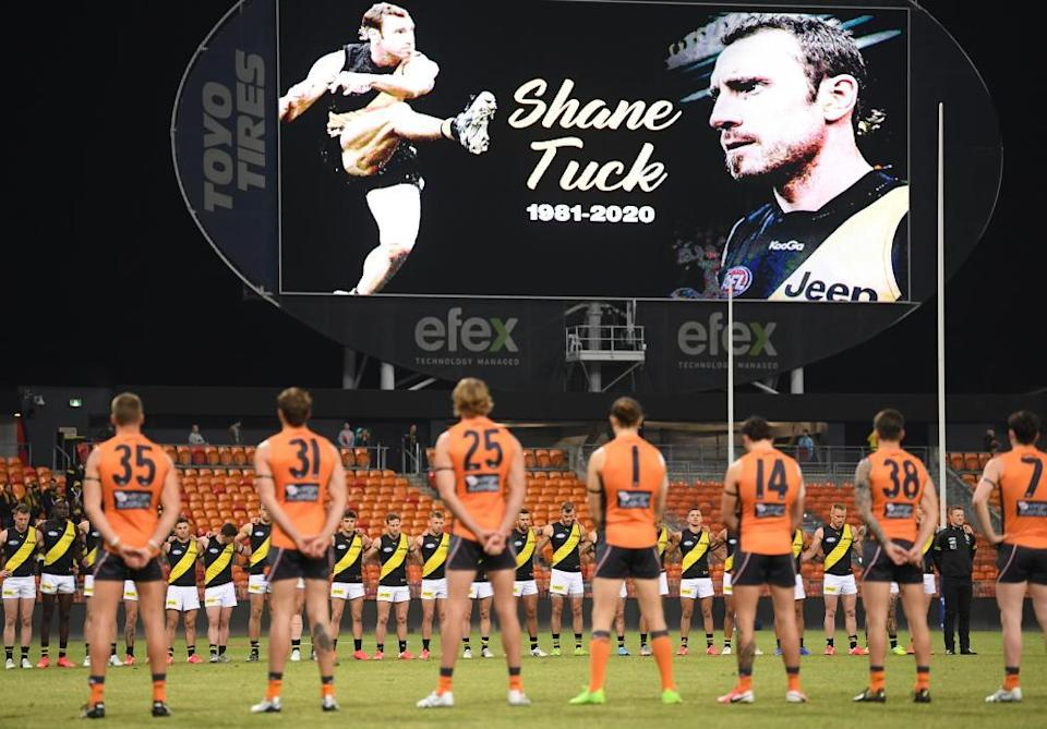 Richmond and GWS players observe a minute's silence in memory of Shane Tuck.