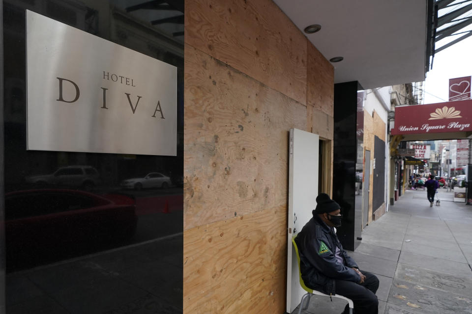 A security guard wears a mask as he sits in front of the entrance to the Hotel Diva in San Francisco, Saturday, Nov. 21, 2020. Some counties in California are pushing ahead with plans to wind down a program that's housed homeless people in hotel rooms amid the pandemic, despite an emergency cash infusion from the state aimed at preventing those same residents from returning to the streets in cold, rainy weather as the virus surges. (AP Photo/Jeff Chiu)