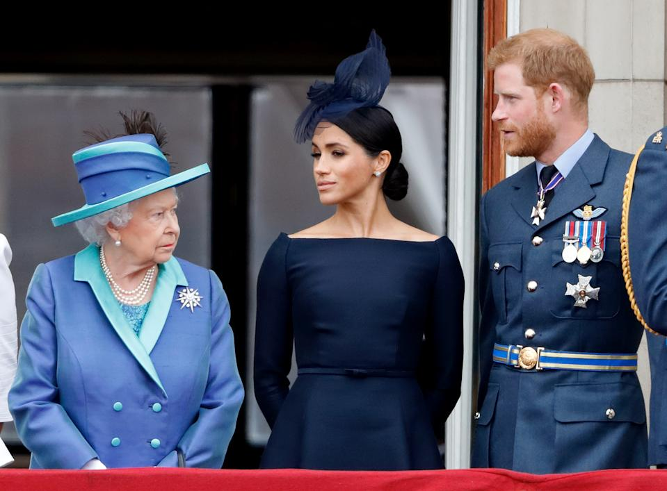 Queen Elizabeth II, Meghan, Duchess of Sussex and Prince Harry, Duke of Sussex watch a flypast to mark the centenary of the Royal Air Force from the balcony of Buckingham Palace on July 10, 2018 in London, England. The 100th birthday of the RAF, which was founded on on 1 April 1918, was marked with a centenary parade with the presentation of a new Queen's Colour and flypast of 100 aircraft over Buckingham Palace.
