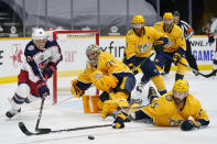 Columbus Blue Jackets right wing Cam Atkinson (13) and Nashville Predators right wing Brad Richardson (15) reach for the puck in the first period of an NHL hockey game Saturday, Jan. 16, 2021, in Nashville, Tenn. (AP Photo/Mark Humphrey)