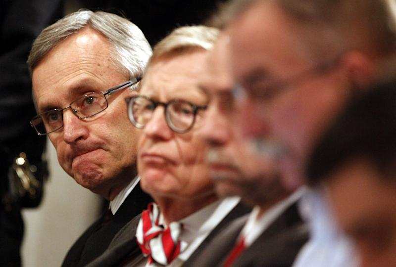"""FILE - In this March 8, 2011 file photo, Ohio State football coach Jim Tressel, left, and university President E. Gordon Gee, second from left, listen as athletic director Gene Smith speaks during a news conference in Columbus, Ohio. As the country absorbs the independent report released Thursday, July 12, 2012, on the Penn State sex abuse scandal, some see it as more than an indictment of one school. They see it as underscoring how major-college sports, football in particular, have run amok. When Gee heard Tressel concede he had reason to believe several star players were taking money and free tattoos from a suspected drug dealer and yet he had told no one, Gee was asked if he had considered firing Tressel. """"Let me just be very clear,"""" Gee said with a grin, """"I'm just hopeful the coach doesn't dismiss me."""" The joke fell flat, but echoed around the country. It confirmed what many already believed about the balance of power in college sports today: some football teams run universities, not the other way around. (AP Photo/Terry Gilliam, File)"""