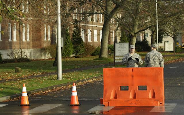 Two soldiers stand guard at a road closed for construction outside the building housing a military courtroom on Joint Base Lewis McChord in Washington state, where a preliminary hearing was expected to conclude Tuesday Nov. 13, 2012, for U.S. Army Staff Sgt. Robert Bales. Bales is accused of 16 counts of premeditated murder and six counts of attempted murder for a pre-dawn attack on two villages in Kandahar Province in Afghanistan last March. (AP Photo/Ted S. Warren)