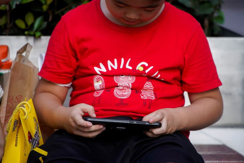 A boy plays a game on a phone on a street in Shanghai