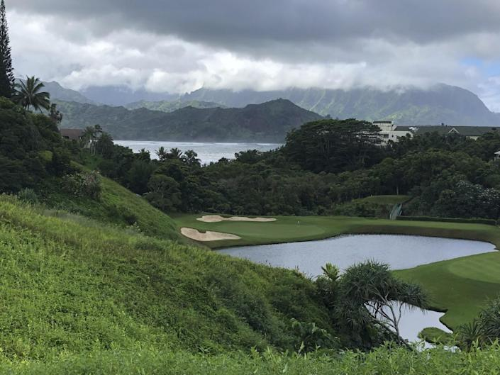 A dark sky above mountains and a golf course covered in deep green grass and trees.