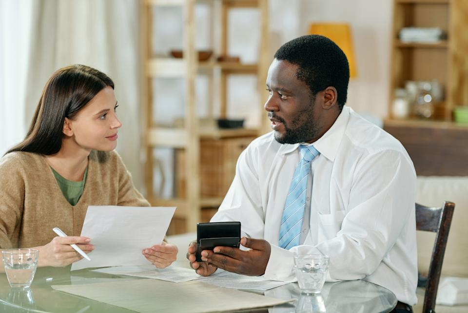 Adult black man and young woman sitting at table and discussing home loan with papers
