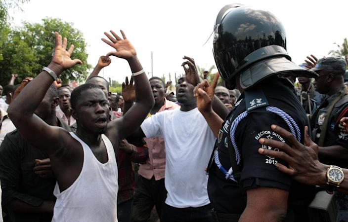 Angry demonstrators argue with police as people protest alleged vote counting irregularities, in Accra, Ghana, Saturday, Dec. 8, 2012. Police fired water cannons and tear gas on hundreds of opposition party supporters who were protesting outside a house where they suspected ballots from the presidential and parliamentary election were being counted by a private company. Electoral commission spokesman Christian Owusu-Parry said the accusations were unfounded. (AP Photo/Christian Thompson)