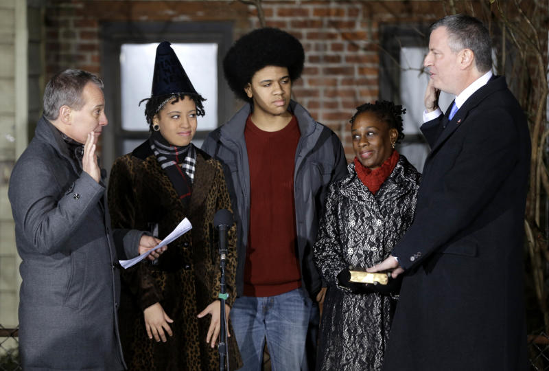 Bill de Blasio, right, is sworn in as the mayor of New York City by State Attorney General Eric Schneiderman, left, while his family, Chiara de Blasio, second from left, Dante de Blasio, center, and Chirlane McCray look on at the start of the new year, Wednesday, Jan. 1, 2014 in New York. De Blasio took the oath of office moments after midnight at his home in Park Slope, Brooklyn. His inauguration will be celebrated at noon Wednesday on the steps of City Hall when he takes the oath again, which will be administered by former President Bill Clinton.(AP Photo/Seth Wenig, Pool)