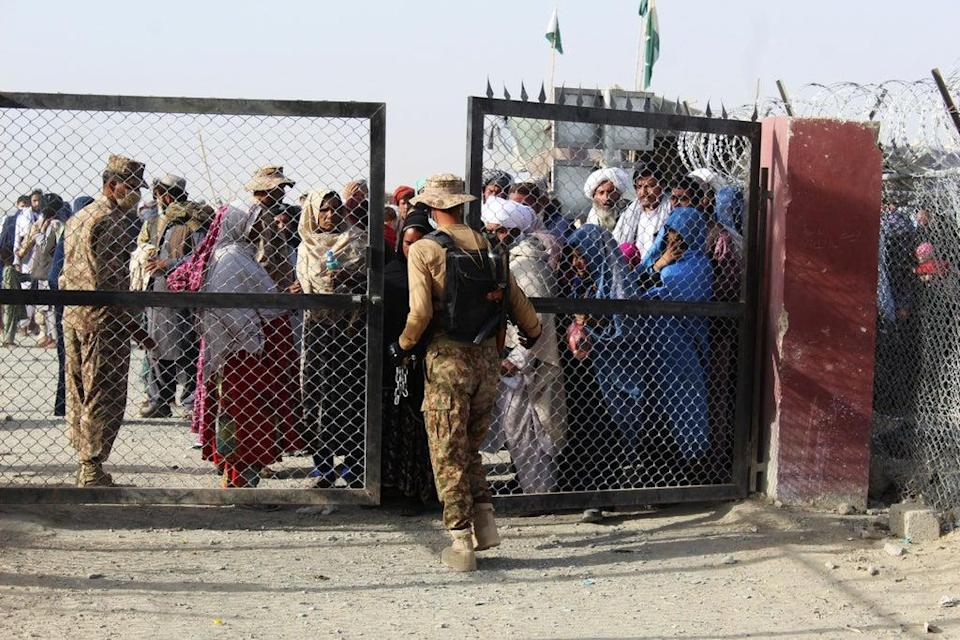 A Pakistani soldier holds a gate as Afghan and Pakistani people wait to enter Afghanistan through the Pakistan-Afghanistan border crossing point in Chaman (AFP via Getty Images)