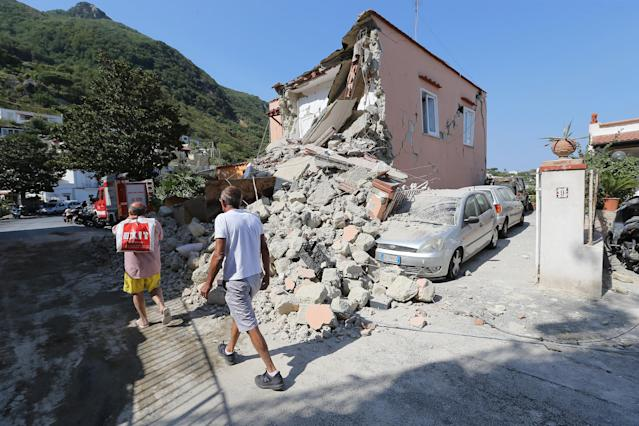<p>People walk near an house destroyed in the earthquake in one of the more heavily damaged areas on Aug. 22, 2017 in Casamicciola Terme, Italy. (Photo: Marco Cantile/NurPhoto via Getty Images) </p>