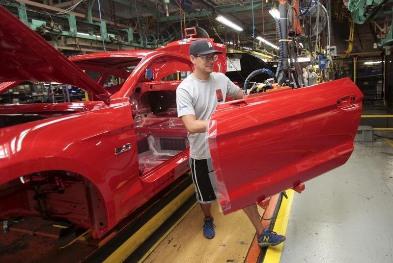 A Ford Motor assembly worker works on a 2015 Ford Mustang vehicle at the Ford Motor Flat Rock Assembly Plant in Flat Rock, Michigan