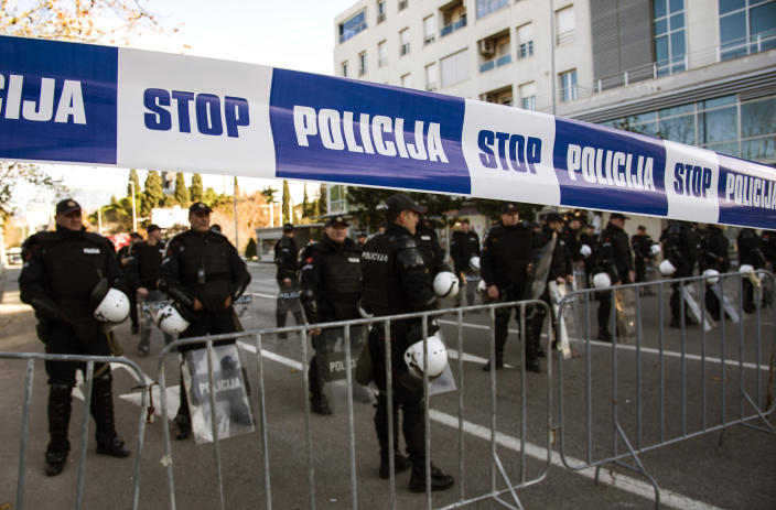 Police officers guard the parliament building in Podgorica, Montenegro, Thursday, Dec. 26, 2019, during a protest against a proposed law regarding religious communities and property. The Serbian Orthodox Church says the law will strip it of its property, including medieval monasteries and churches. The government has denied that. (AP Photo/Risto Bozovic)