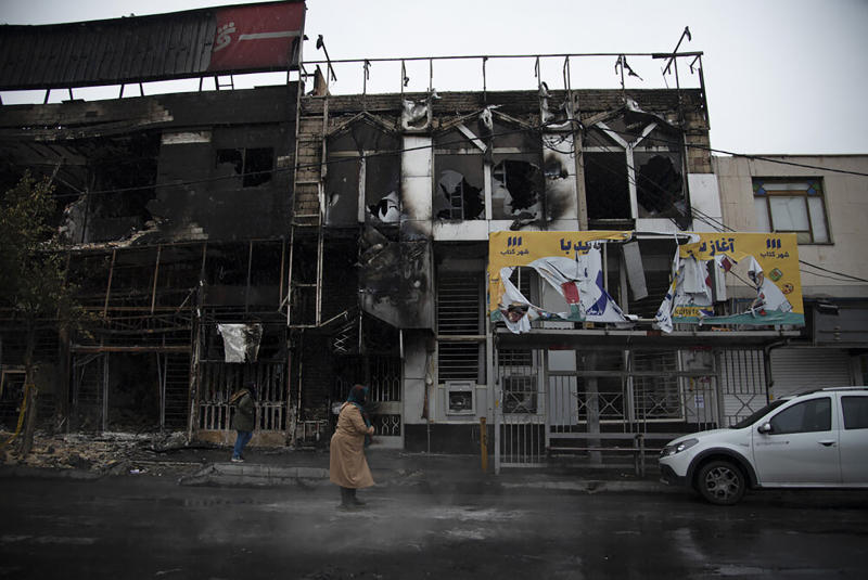 In this photo taken Monday, Nov. 18, 2019, and released by Iranian Students' News Agency, ISNA, people walk past buildings which burned during protests that followed the authorities' decision to raise gasoline prices, in the city of Karaj, west of the capital Tehran, Iran. An article published Tuesday in the Keyhan hard-line newspaper in Iran is suggesting that those who led violent protests will be executed by hanging as the unrest continues. (Masoume Aliakbar/ISNA via AP)