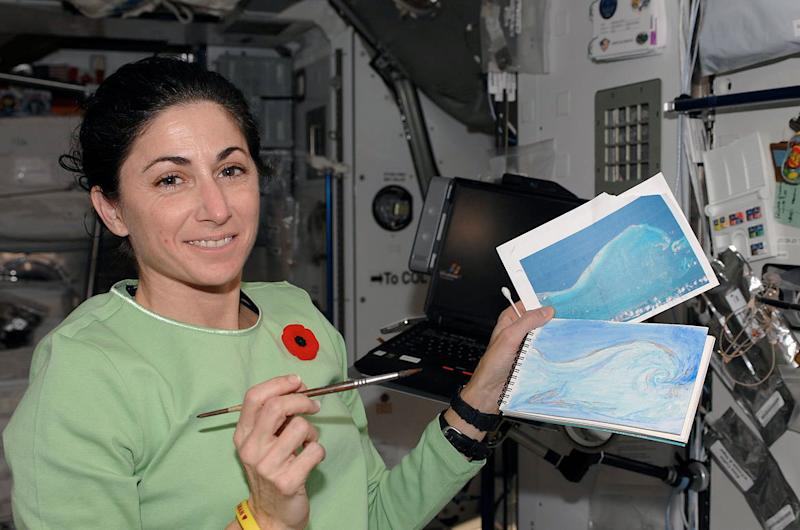 Nicole Stott with her original photo and watercolor painting as she created aboard the space station in 2009. Six years later, Stott left NASA to become a full-time artist.