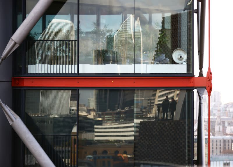Visitors to the Viewing Level at the Tate Modern gallery are reflected in the window of a luxury block of flats in London