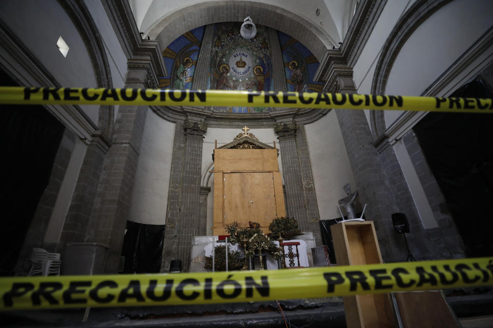 Caution tape seals off the less damaged church apse, where a treasured 400-year-old painting of Our Lady of Angels has been temporarily protected with a wooden cabinet, during the early stages of reconstruction work at Nuestra Senora de Los Angeles, or Our Lady of Angels church, three years after an earthquake collapsed nearly half of its 18th-century dome in Mexico City, Tuesday, Oct. 6, 2020. It is so dangerous to stand beneath the remains of the dome that the tons of steel structures are made off-site and then gingerly lowered into the crater at the center where the dome once stood. (AP Photo/Rebecca Blackwell)