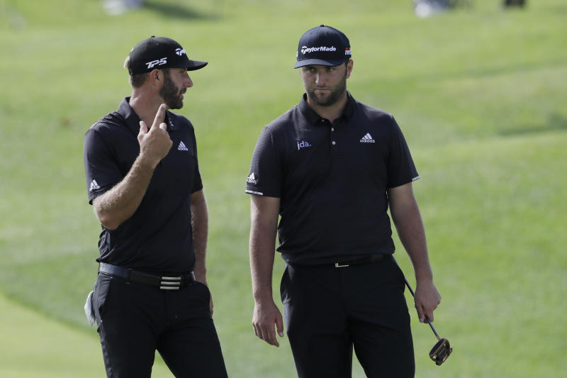 Dustin Johnson, left, talks with Jon Rahm, of Spain, during the first round of the Northern Trust golf tournament at Liberty National Golf Course, Thursday, Aug. 8, 2019, in Jersey City, N.J. (AP Photo/Mark Lennihan)