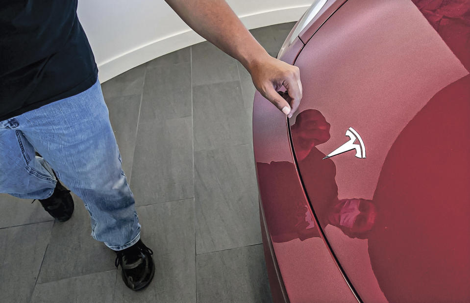 In this Sept. 9, 2021 photo, Dietrich Ginocchio rubs a smudge off the Tesla emblem on a Tesla Y model during an event to celebrate a partnership between Tesla and the Nambé Pueblo after the electric car company repurposed a defunct casino into a sales, service and delivery center near Santa Fe, N.M. Tesla has opened a store on tribal land in New Mexico, sidestepping car dealership laws that prohibit car companies from selling directly to customers. (Jim Weber/Santa Fe New Mexican via AP)