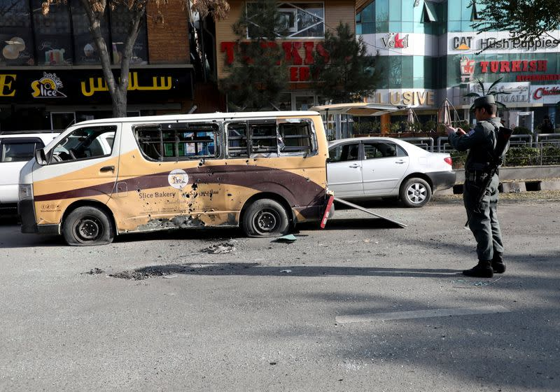 A police officer takes pictures of a damaged vehicle after rockets hit residential areas in Kabul