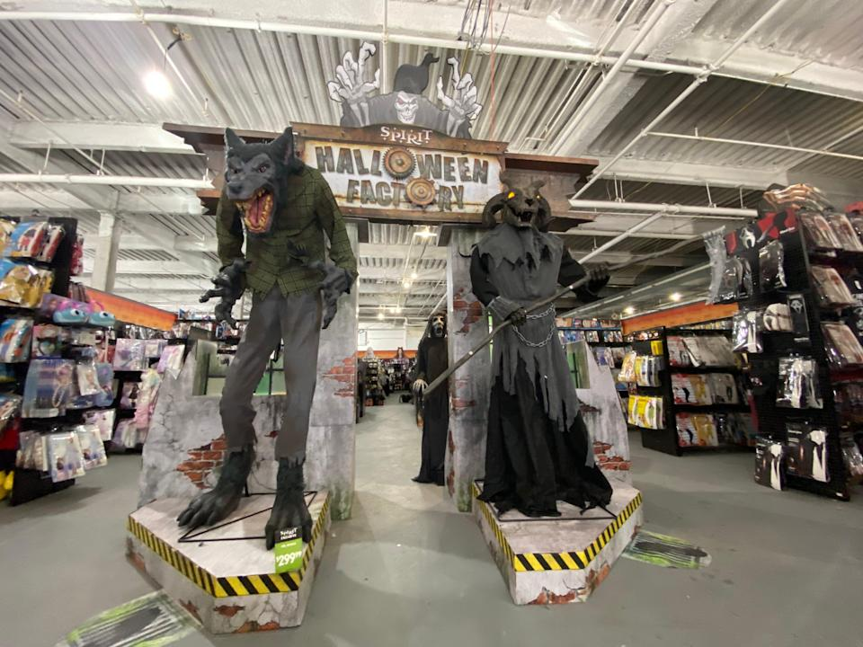 Two large statues and an entryway into spirit Halloween