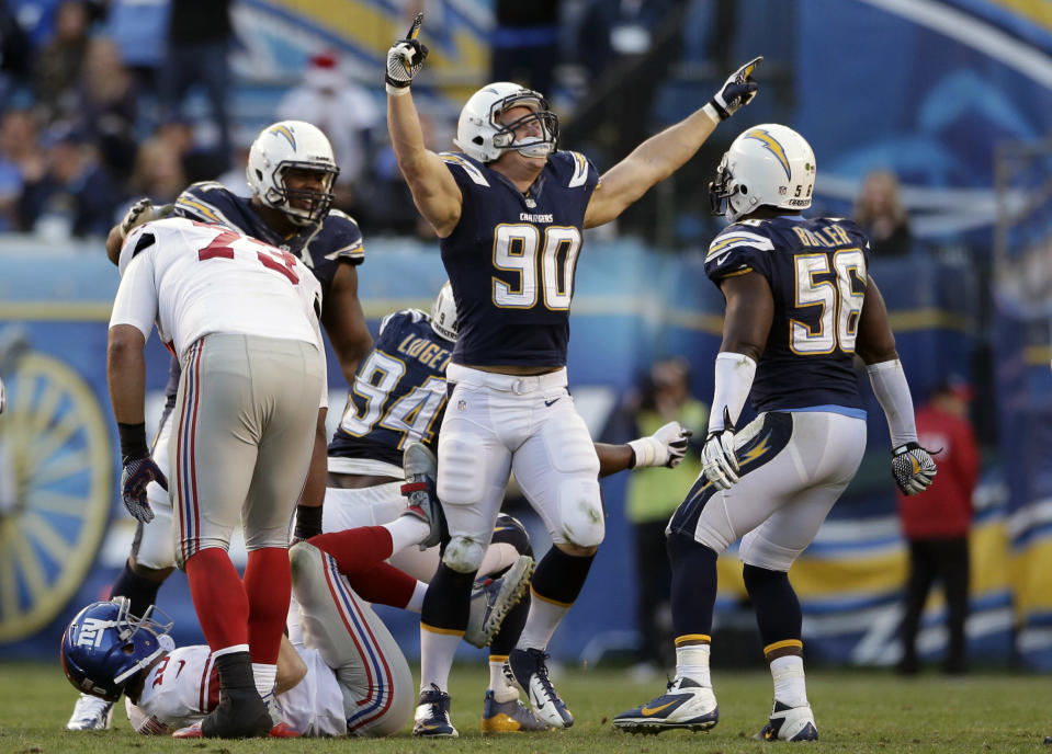 San Diego Chargers linebacker Thomas Keiser (90) celebrates his sack of New York Giants quarterback Eli Manning, bottom left, who is helped back up by teammate James Brewer (73) during an NFL football game on Sunday, Dec. 8, 2013, in San Diego. The Chargers won 37-14. (AP Photo/Gregory Bull)