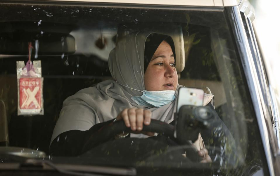 The first female Palestinian taxi driver in the Gaza Strip, Nayla Abu Jubbah, 39, sits at her vehicle as she works in Gaza City.