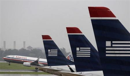 An American Airlines jet takes off while U.S. Airways jets are lined up at Reagan National Airport in Washington